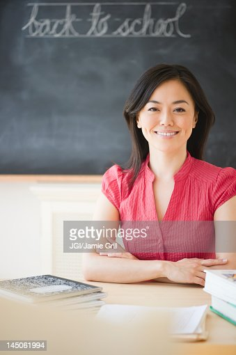 Japanese Teacher Sitting At Desk In Classroom Stock Photo -3375
