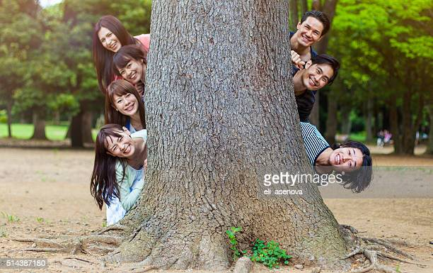 Japanese teenagers peeking out from behind a tree, Tokyo.