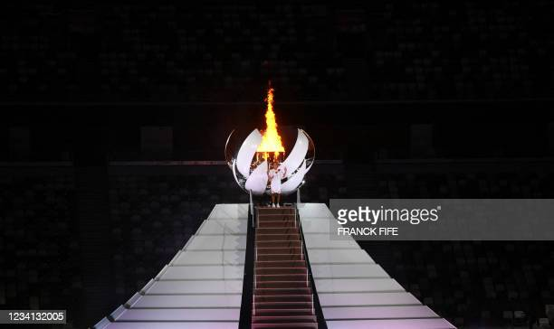 Japanese tennis player Naomi Osaka holds the Olympic Torch after lighting the flame of hope in the Olympic Cauldron during the opening ceremony of...