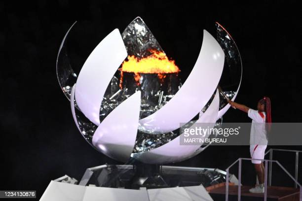 Japanese tennis player Naomi Osaka lights the flame of hope in the Olympic Cauldron during the opening ceremony of the Tokyo 2020 Olympic Games, at...