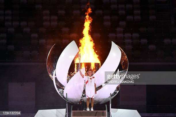 Japanese tennis player Naomi Osaka poses after lighting the Olympic Cauldron with the Olympic flame during the opening ceremony of the Tokyo 2020...