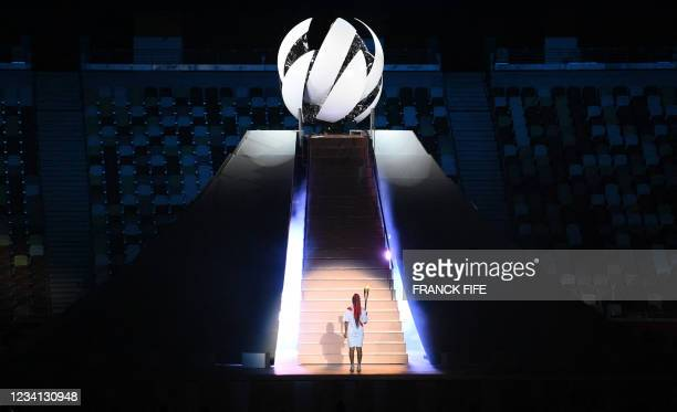 Japanese tennis player Naomi Osaka prepares to light the flame of hope in the Olympic Cauldron during the opening ceremony of the Tokyo 2020 Olympic...
