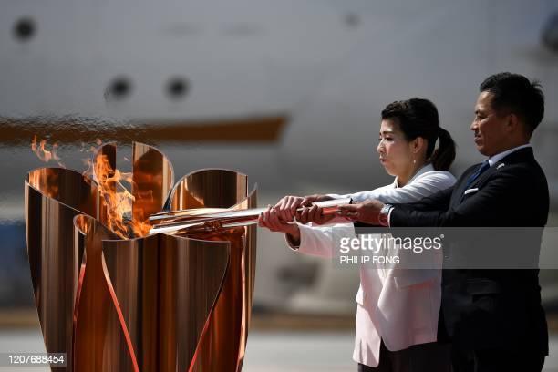 Japanese three-time Olympic gold medallists Saori Yoshida and Tadahiro Nomura light a Tokyo 2020 Olympic cauldron with the Olympic flame, after...