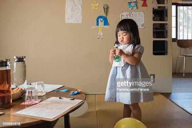 日本の幼児の女の子調べるバルーン、バースデーパーティの準備をいたします。