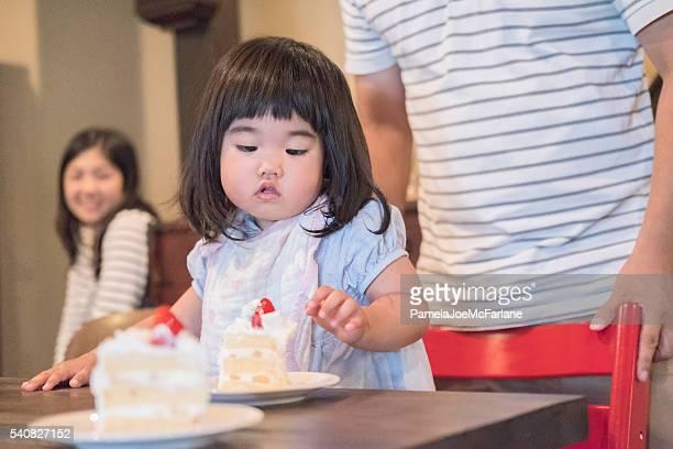 日本の幼児の女の子のケーキを食べ、ご家族での背景