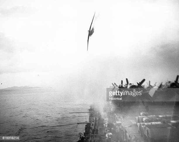 """Japanese """"Toni"""" making a suicide dive on the USS Sangamon at Kerama Retto in Okinawa Gunto. The plane missed the ship by about 25 feet. May 4, 1945."""