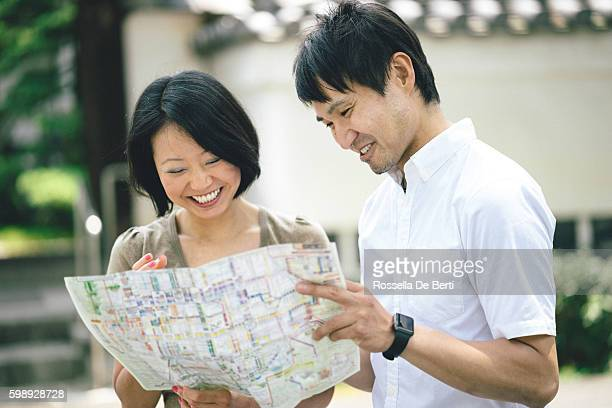 Japanese tourist couple visiting Kyoto looking at map