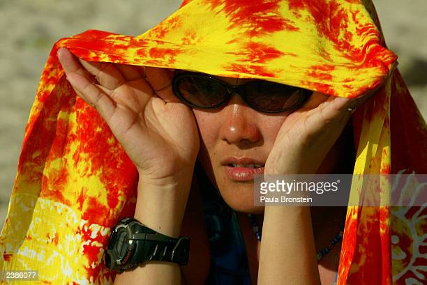 Japanese tourist covers herself from the sun after getting sunburnt on Kuta beach August 10 2003 in Bali Indonesia Bali depends on tourism which has...