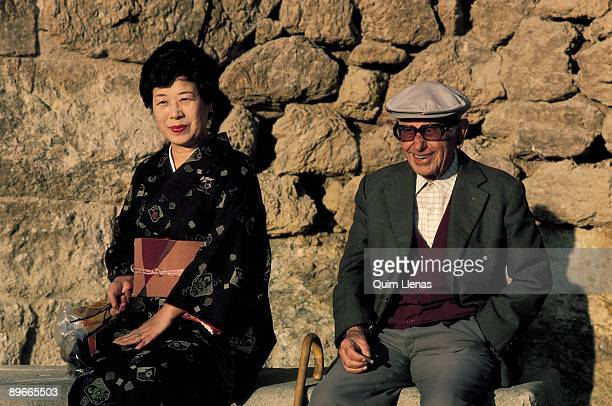 Japanese tourist in the Guell park Barcelona A Japanese tourist is seated next to an old man smiling on a wall of the Guell Park in Barcelona
