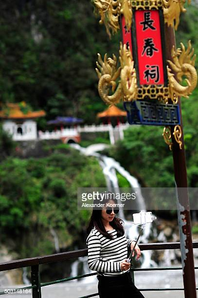 Japanese tourist takes a selfie in front of the Eternal Spring Shrine at a canyon above the Leewo Ho River inside Taroko National Park on January 2,...
