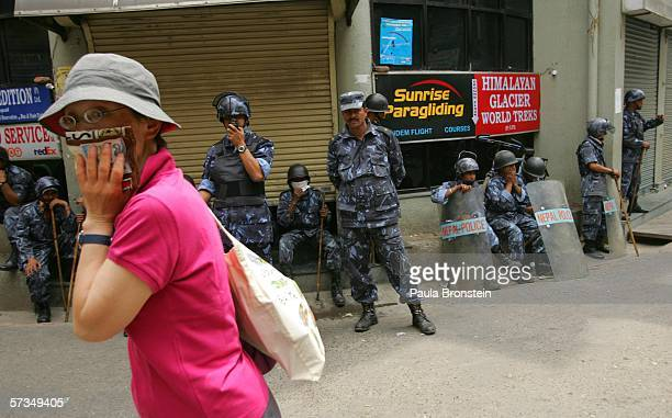 Japanese tourist walks by Nepaleses armed police standing by after a demonstration in the tourist area of Thamel protesting the rule of King...