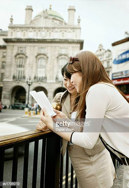 Japanese Tourists Looking at a Map at Piccadilly Circus, London, UK