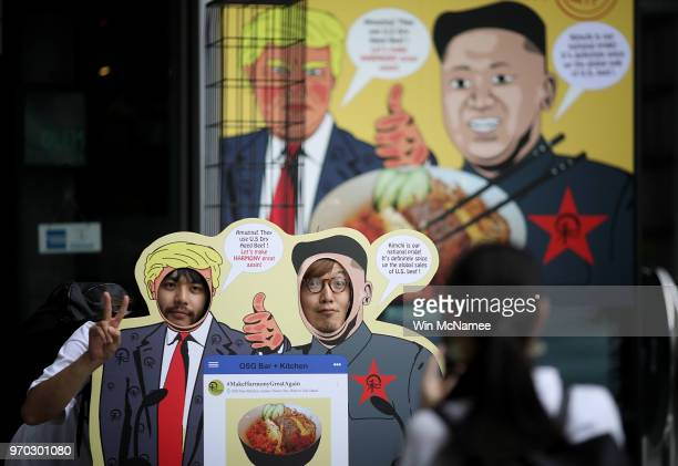 Japanese tourists pose outside a restaurant featuring a dish marking the scheduled meeting between US President Donald Trump and North Korean leader...