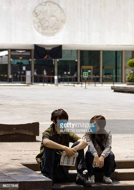 Japanese tourists sitting outside the Anthropology Museum in Mexico City wear surgical masks to ward off infection by the new multistrain swine flu...
