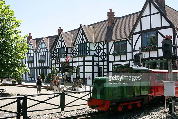 Japanese tourists stand in front of Englishstyled buildings at an English Village theme park on August 10 2003 in Shuzenji ShizuokaPrefecture Japan...