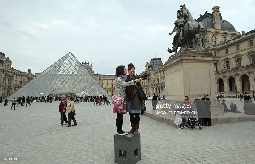 Japanese tourists take photos of themselves while people queue at the entrance of the Louvre Museum during the 6th edition of the 'Nuit des musees' (Museum night) yearly event on May 15, 2010 in Paris. During this cultural event, various museums in France and in Europe will remain open late night and let free access to visitors.
