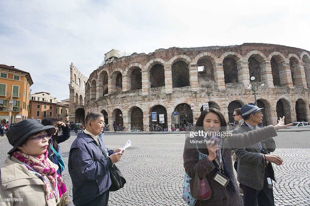Japanese tourists take pictures of the amphitheatre as tickets for the 2014 Opera Festival at the Arena are on sale on March 27, 2014 in Verona, Italy. For the 2014 Festival 6 different operas and 3 special events will be presented, for a total of 54 performances.