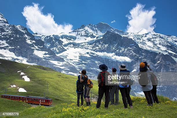 Japanese tourists viewing the Jungfrau mountain peak as avalanche rumbles in the Swiss Alps in Bernese Oberland Switzerland