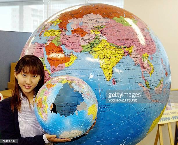 Japanese toy maker Yanoman employee Akiko Otomo displays a threedimensional jigsaw puzzle shaped globe in 12inch or 305cm diamter before a large...