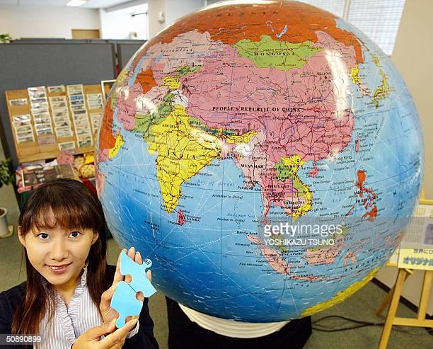 Japanese toy maker Yanoman employee Akiko Otomo displays a piece of a large threedimensional jigsaw puzzle shaped globe which has 15meter diameter...