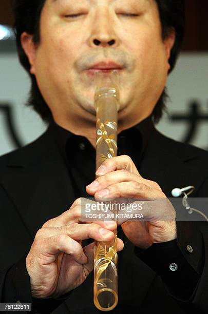 Japanese traditional bamboo flute or shakuhachi player Gazan Watanabe plays a glassmade shakuhachi during a press preview at a Tokyo hotel 28...