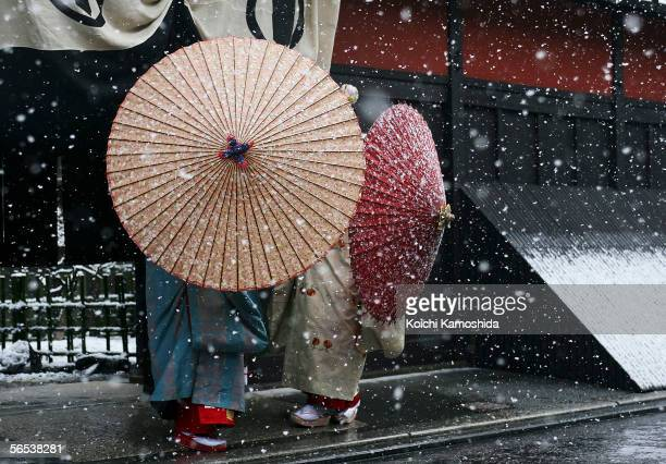 Japanese traditional dancers walk in the snow in Gion Kyoto's famous geisha district January 7 2006 in Kyoto Japan The ancient city Kyoto attracts...