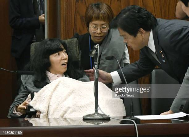 Japanese transport minister Kazuyoshi Akaba talks to lawmaker Eiko Kimura who has cerebral palsy after her first interpellation at an upper house...