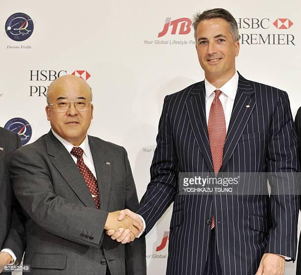 Japanese travel agency JTB president Hiromi Tagawa shakes hands with