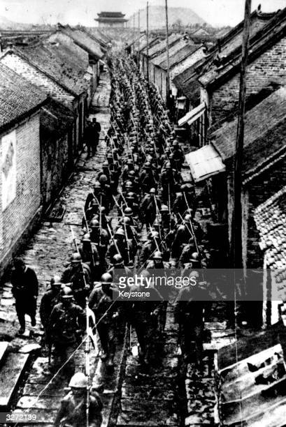 Japanese troops marching through a street in Manchuria during the SinoJapanese war