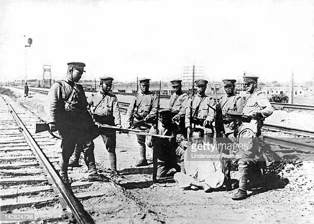 Japanese troops question a captured Chinese man in Manchuria for information about the fleeing Chinese troops, Mukden, Manchuria, early to mid 1930s....