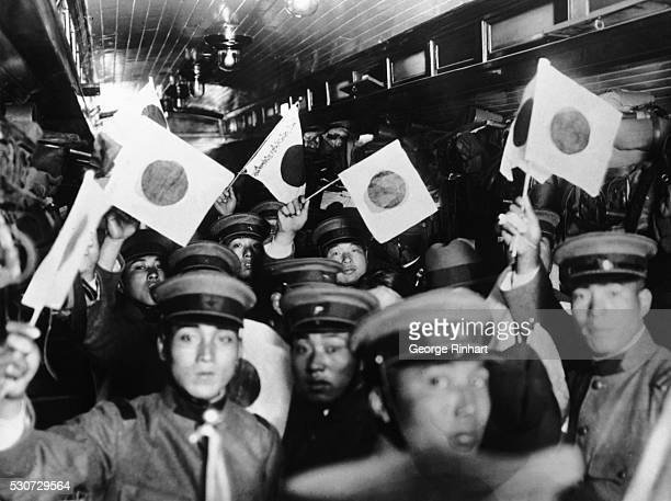 Japanese troops wave small Japanese flags as they leave Tokyo in a train bound for Manchuria site of the SinoJapanese conflict