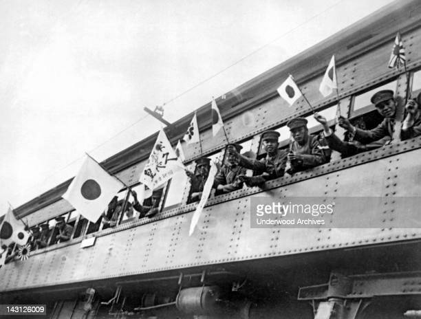 Japanese troops waving flags and banners as they are leaving the Japanese capital for Manchuria, the site of the present Sino-Japanese conflict,...
