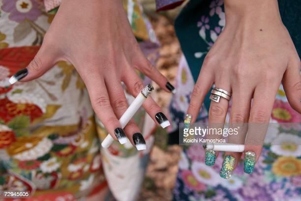 Japanese twentyyearold girls dressed in traditional attire smoke a cigarette as they visits the Heianjingu Shrine as they celebrate comingofage on...