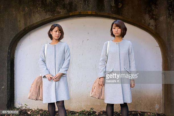 Japanese twin sisters standing in front of wall
