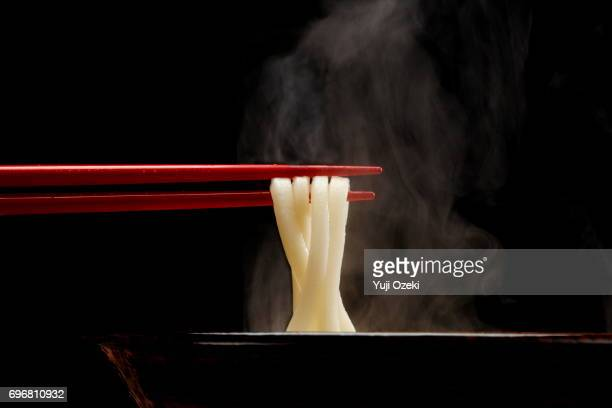 Japanese Udon noodle lifted up by red chopsticks with steam against black background