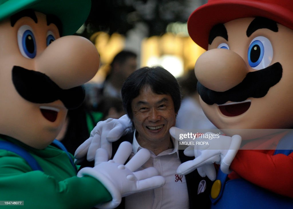 Japanese video game designer Shigeru Miyamoto (C) smiles as he poses with arcade game stars Mario Bros and Luigi at the Jovellanos Theatre in Gijon, on October 25, 2012, to participate in a tribute to the video game, on the eve of the Prince of Asturias 2012 Award ceremony. Miyamoto has been awarded with the Prince of Asturias Award for Communication and Humanities.