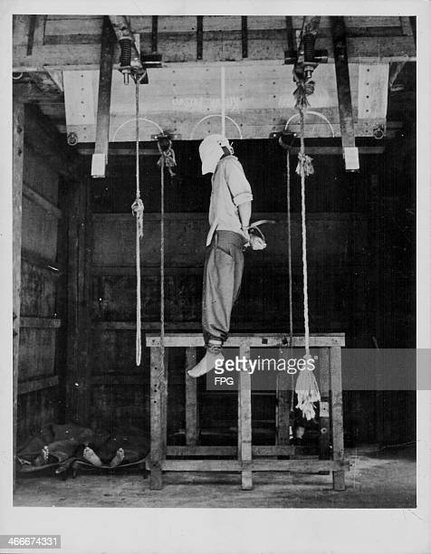 Japanese war criminals being hung following World War Two; Cpt. Kamai Mitsuo dangles from the gallows, with Sgt. Eishima and Lt. Nakamura already...