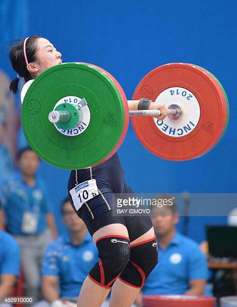 Japanese weightlifter Andoh Mikiko competes during the women's 58kg group A at the Moonlight Festival Garden Weightlifting Venue during the 2014...