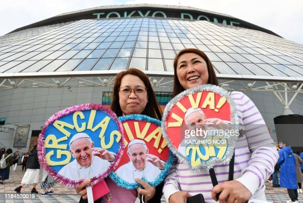 Japanese wellwishers show merchandise printed with images of the Pope outside the Tokyo Dome stadium ahead of a holy mass led by Pope Francis in...