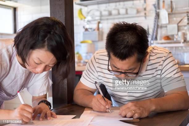 日本人の妻と夫キッチンで文書を完了し、署名 - 日本語の文字 ストックフォトと画像