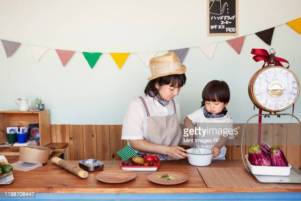 japanese woman and boy standing in a farm shop, preparing food. - 日本人のみ ストックフォトと画像