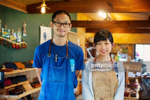 japanese woman and man wearing blue apron standing in a leather shop, smiling at camera. - ショッピングエリア ストックフォトと画像