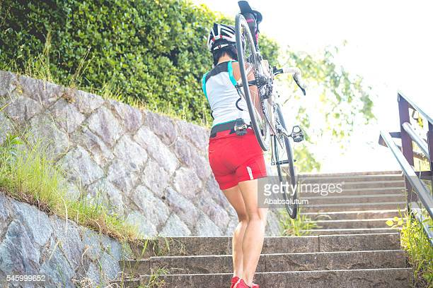 japanese woman carrying bike on shoulders in kyoto city, japan - lypsekyo16 stock pictures, royalty-free photos & images