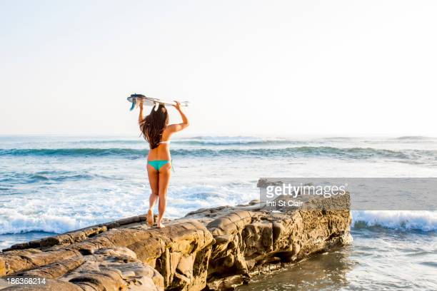 Japanese woman carrying surfboard on beach