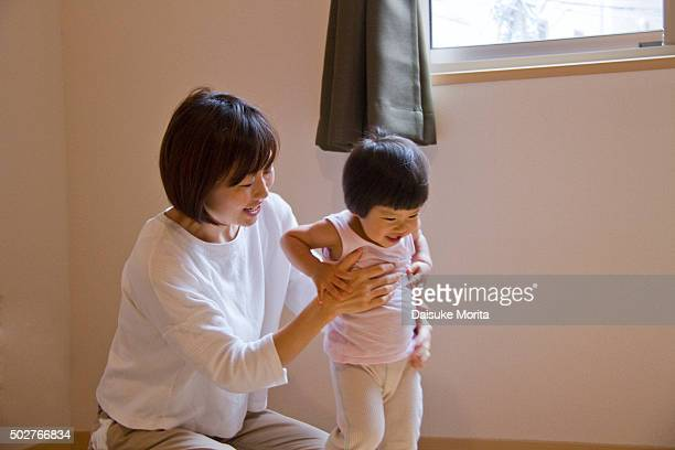 Japanese woman changing of her daughter's clothes