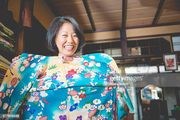 japanese woman choosing blue floral fattern kimono in kyoto, japan - lypsekyo16 stock pictures, royalty-free photos & images