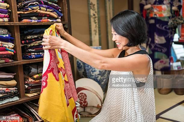 japanese woman choosing yellow kimono in kyoto, japan - lypsekyo16 stock pictures, royalty-free photos & images