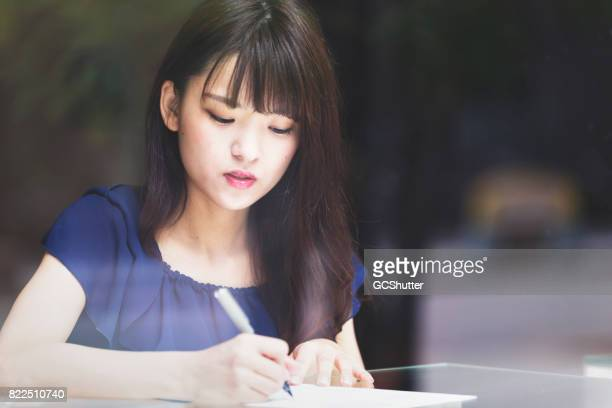 japanese woman completing an application - college application stock photos and pictures