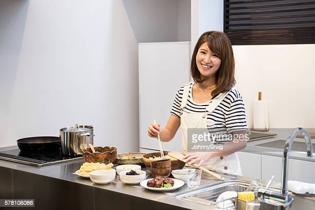 Japanese woman cooking dinner at home, smiling