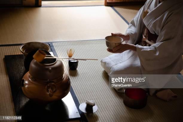 japanese woman cradling bowl in tea ceremony - cerimonia foto e immagini stock